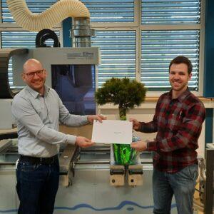 Luca Föhn (r.) erhält von Dr. Cornelius Oesterlee die Auszeichnung von Swiss Timber Engineers STE für die innovativste Bachelorthesis überreicht.